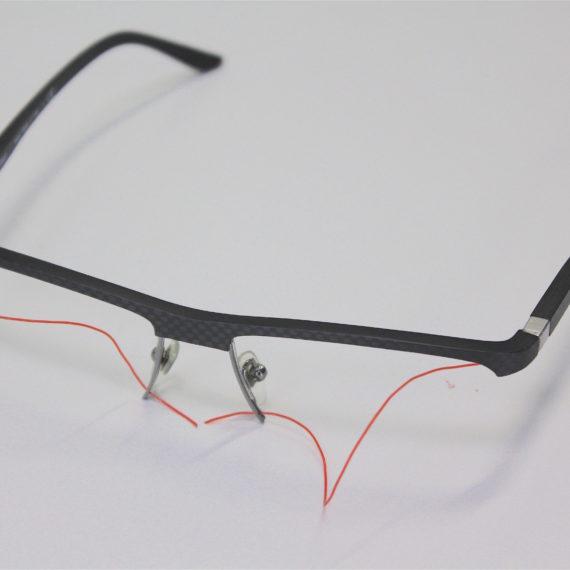 Remplacement d'un fil translucide par un  rouge lors du montage des verres sur ces lunettes Starck.